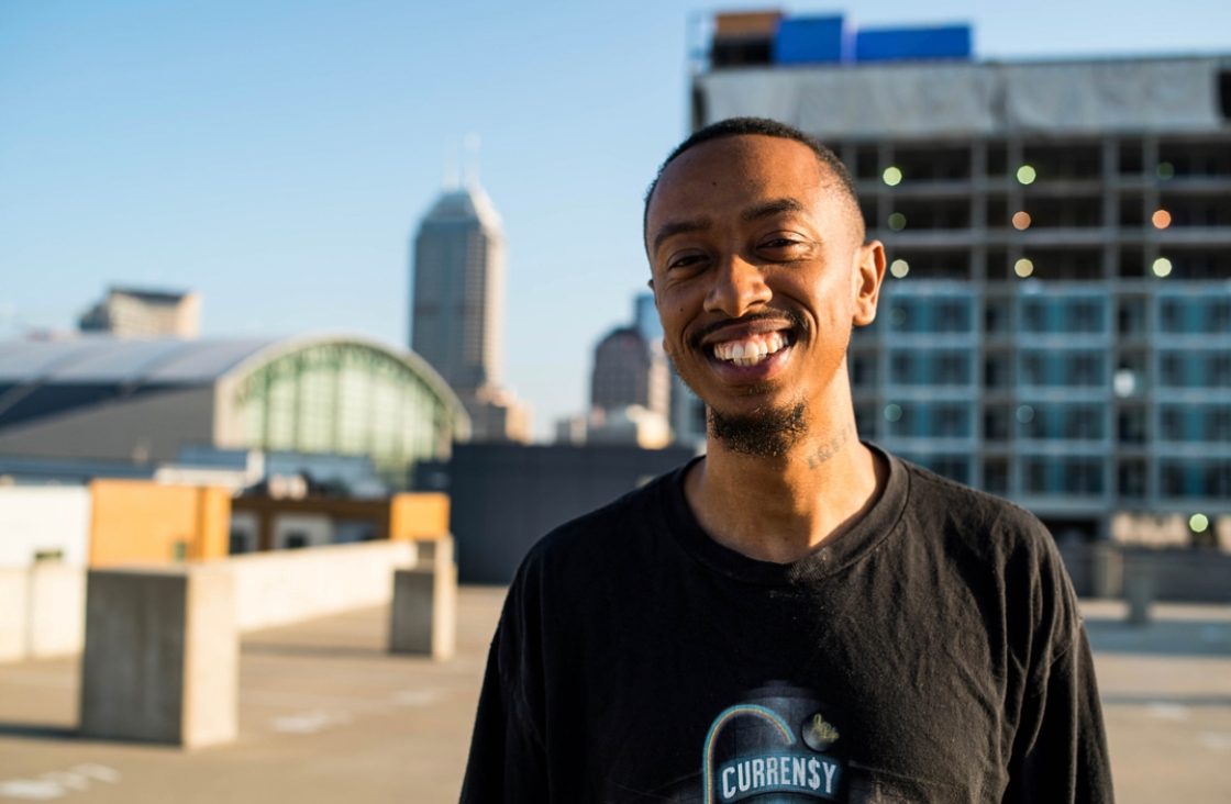 musician diop poses in front of indianapolis skyline
